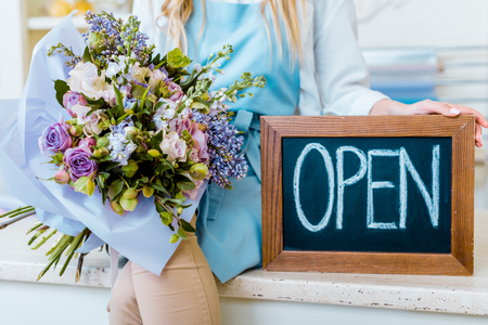 cropped view of female flower shop owner holding chalkboard with 'open' lettering and colorful bouquet