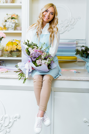 beautiful happy female flower shop owner looking at camera, sittng on counter and holding bouquet
