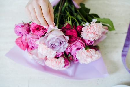 cropped view of female florist arranging bouquet with pink roses and carnations