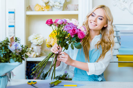 beautiful smiling female florist arranging bouquet in flower shop Stok Fotoğraf - 117398838