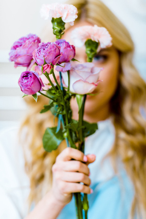 woman holding pink roses and carnations in front of face