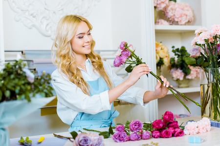 attractive female florist in apron arranging bouquet with roses in flower shop Stok Fotoğraf - 117398847