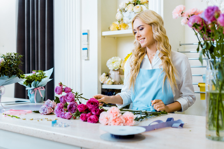 beautiful happy female florist in apron arranging bouquet with roses in flower shop