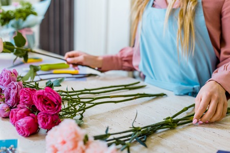 cropped view of female florist sitting at table with pink roses and carnations while arranging bouquet