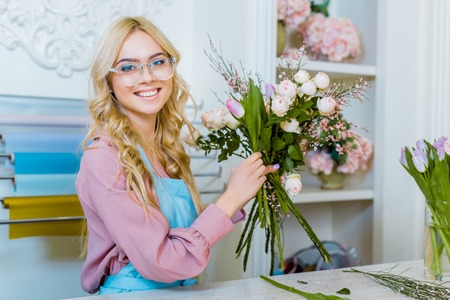 beautiful female florist in glasses arranging bouquet and looking at camera in flower shop Stok Fotoğraf - 117437730