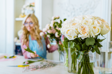 selective focus of white roses with female florist in flower shop on background