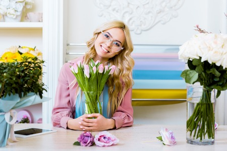 beautiful female florist looking at camera and holding vase with pink tulips in flower shop
