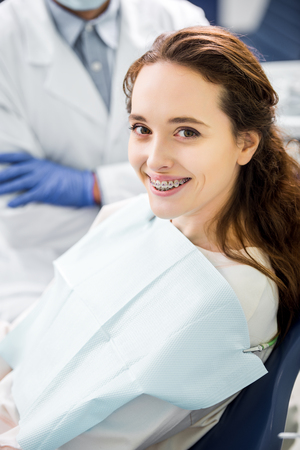 selective focus of woman in braces smiling with dentist standing with crossed arms on background Banco de Imagens