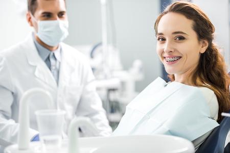 El enfoque selectivo de la mujer en frenillos sonriendo con dentista de pie en la máscara en el fondo