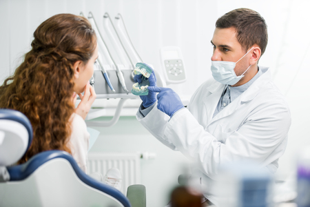 selective focus of dentist in mask and latex gloves pointing with finger at teeth model near female patient Standard-Bild