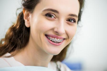 Cerca de mujer feliz con frenillos en los dientes sonriendo en la clínica dental Foto de archivo