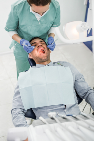 female dentist in mask working with patient with opened mouth