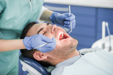 cropped view of dentist in latex gloves examining patient with opened mouth Stock Photo