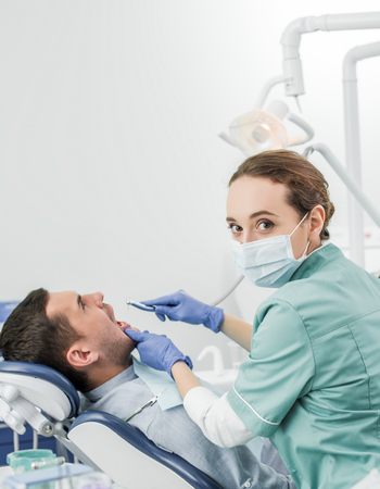 dentist in mask holding dental drill while working with patient in dental clinic