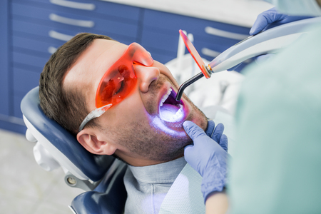 cropped view of dentist making whitening procedure to patient in glasses Stock fotó