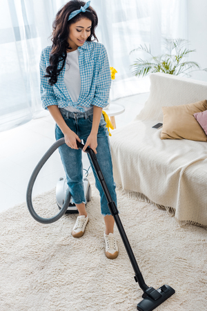 beautiful african american woman cleaning carpet with vacuum cleaner