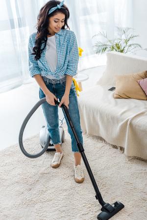 Hermosa mujer afroamericana limpieza de alfombras con aspiradora