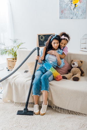 adorable african american child hugging tired mother sitting on sofa 版權商用圖片