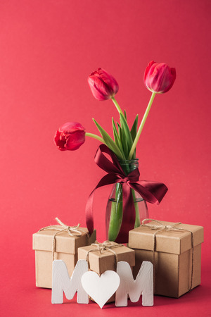 gift boxes, bouquet of red tulips with red satin bow and paper word mom with heart shaped litter