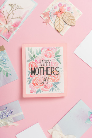 happy mothers day greeting card with flowers, and various mothers day postcards arranged around on pink background Banco de Imagens