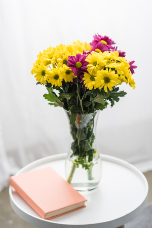 Fresh flowers and book on white table Banco de Imagens