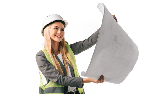 cheerful female architect in safety vest and hardhat working with blueprint, isolated on white