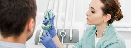 selective focus of female dentist holding teeth model and toothbrush near patient
