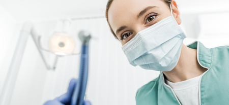 selective focus of female dentist in mask and latex gloves holding dental drill 写真素材 - 117398801