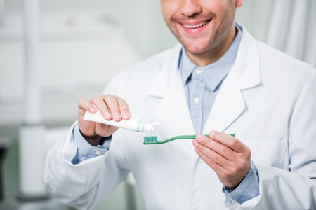 cropped view of smiling dentist squeezing toothpaste on toothbrush in dental clinic Stock Photo