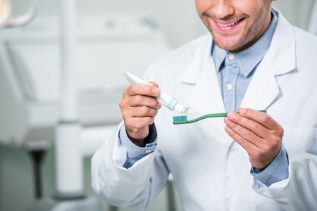 cropped view of happy dentist squeezing toothpaste on toothbrush in dental clinic Stock Photo