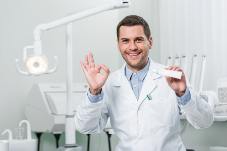 dentist holding toothpaste and showing ok sign in dental clinic Stock Photo