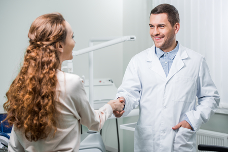 woman shaking hands with dentist standing with hand in pocket