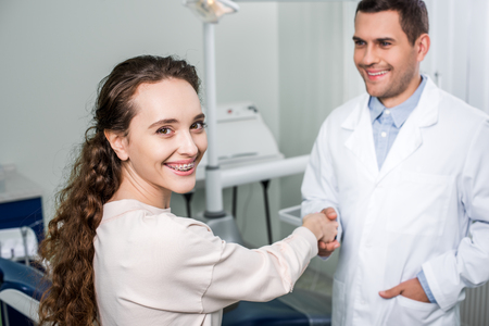 selective focus of cheerful woman in braces shaking hands with dentist standing with hand in pocket 写真素材 - 117398886