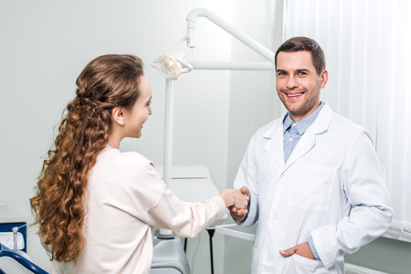 smiling dentist standing with hand in pocket and shaking hands with female patient Stok Fotoğraf