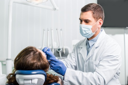 dentist in mask working with woman in latex gloves in dental clinic