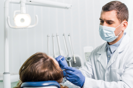dentist in latex gloves and mask working with woman in clinic