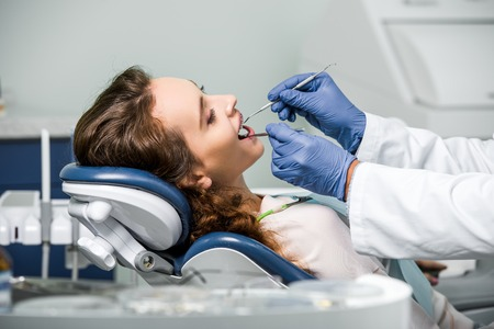 cropped view of dentist in latex gloves examining teeth of woman in dental clinic 스톡 콘텐츠