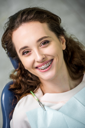 cheerful woman in braces smiling during examination in dental clinic