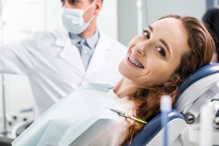 selective focus of beautiful woman in braces during examination of teeth near dentist Banque d'images