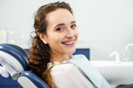 Mujer feliz en llaves sonriendo durante el examen en la clínica dental