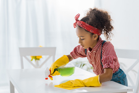 cute african american child in yellow rubber gloves washing table with cleaning spray and rag