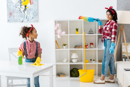 cute african american child cleaning table while mother dusting shelving unit Stock Photo