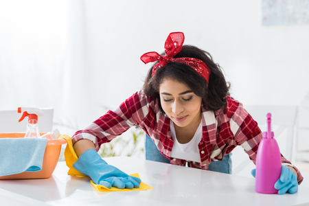 pretty african american woman in plaid shirt cleaning table