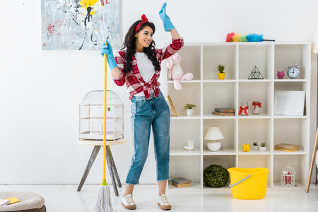 cheerful african american woman in plaid shirt and blue rubber gloves dancing with mop