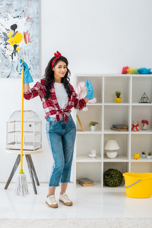 pretty african american woman in plaid shirt and blue rubber gloves standing with mop