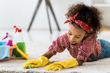 cute african american child cleaning carpet in yellow rubber gloves Stock Photo