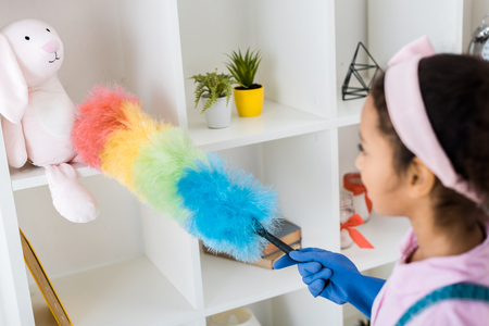 cute african american kid dusting shelving unit with multicolored duster Stock Photo