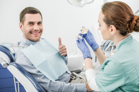 selective focus of happy man showing thumb up near female dentist holding teeth model Stockfoto