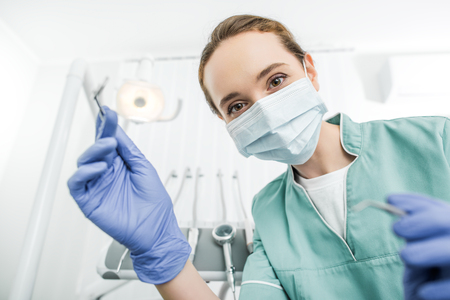 selective focus of female dentist in latex gloves and mask holding dental instruments 写真素材