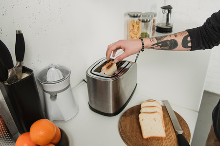 cropped view of tattooed man preparing toasts with toaster during breakfast in kitchen